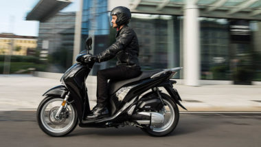 a man riding a black Honda SH150 scooter for rent in Sydney from Scootering
